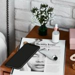 Beauty Items Over Magazine On Bedside Table